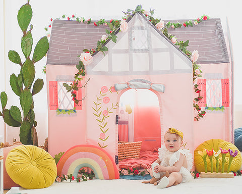 Little girl sitting in front of Dream House