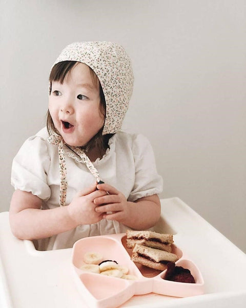 Cute asian girl excited about here mealtime mabel silicone suction plate from giggle bee