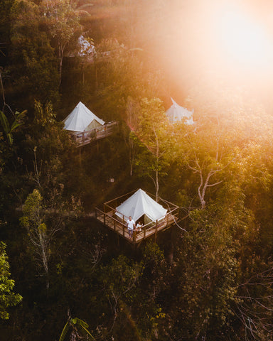 Image of 3 glamping tents on wooden platforms in nature.