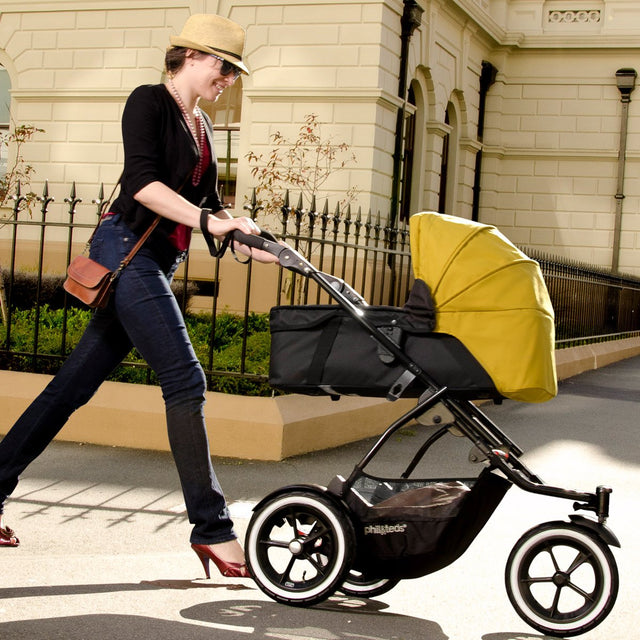 phil&teds 2015-2019 snug carrycot on buggy being pushed by mother walking in a city street_black