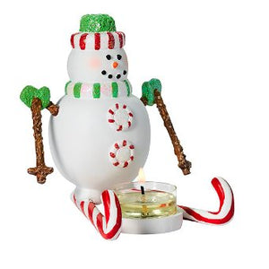 "Merry Mint is a snowman with colorful style, including a delightful candy cane skis and gum drop buttons. This resin tealight candle holder is designed to fit any tealight in your choice of fragrance. Resin. 12 cm h, 12 cm w. 4 ¾"" h, 4 ¾"" w."