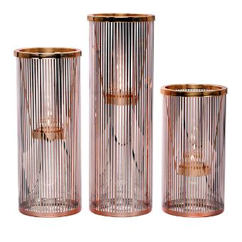 Pinstripe Glam Tealight Holder Trio, a set of 3 glass holders with metallic rose gold pinstripe detail. They include matching metal tealight hangers. Each /set includes one each of 3 heights: 28 cm h; 23 cm h; 18 cm h.