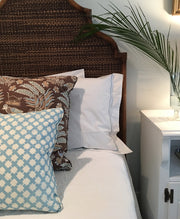 headboard with throw pillows and bed linens