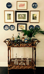 beverage stand and serving table against wall with framed art work above