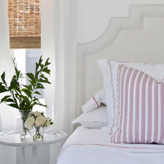 faux white roses next to bed with pink and white striped pillow and bed linens with pink stripe