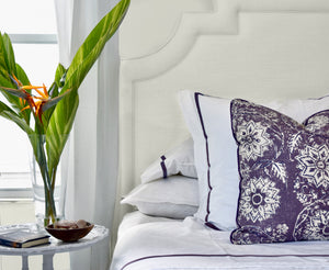 lavender floral throw pillow on bed with luxury bed linens
