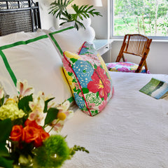 faux flowers next to bed with throw pillow and luxury bed linens and headboard
