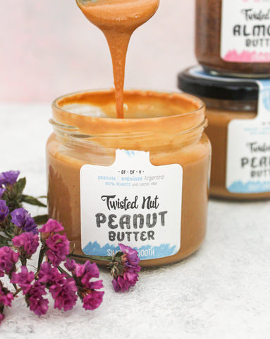 A spoon of the silky smooth peanut butter by Twisted Nut coming out of the jar.