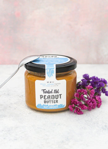 A jar of Twisted Nut's Silky Smooth Peanut Butter with a Spoon on Top