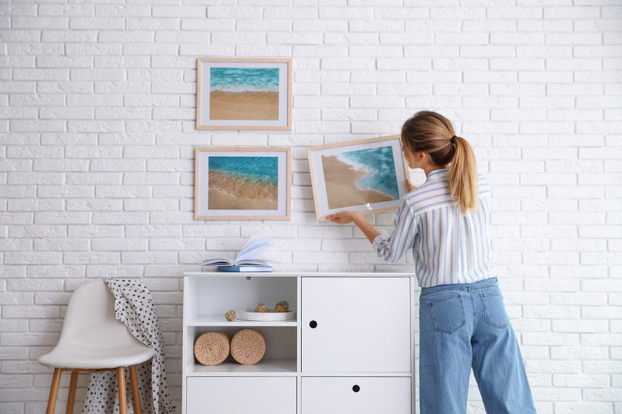 Decorator hanging picture on white brick wall