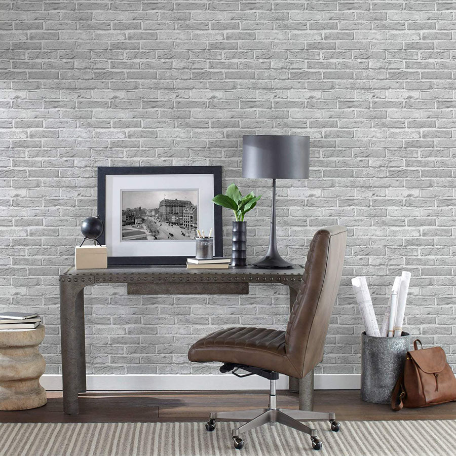 a home office featuring white brick peel and stick wallpaper
