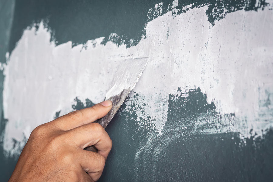 a person applying white spackle to a wall