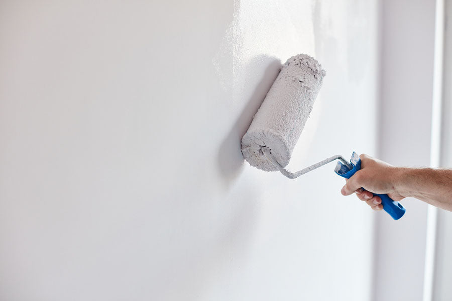 someone applying white paint with a paint roller