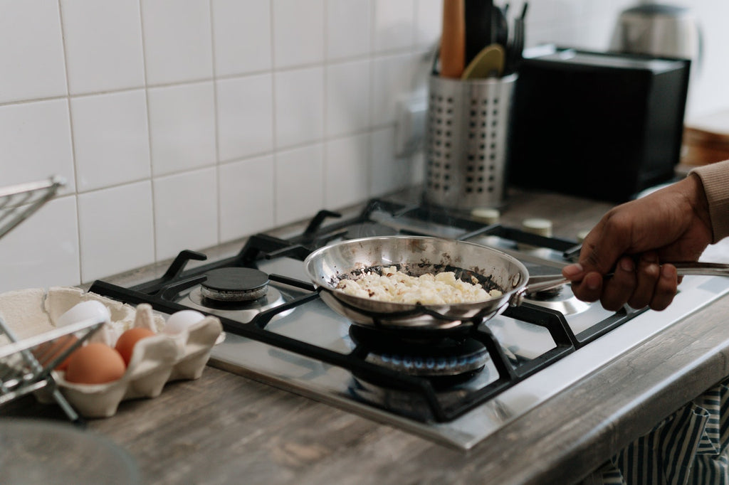 person holding stainless steel cooking pan on gas cooktop