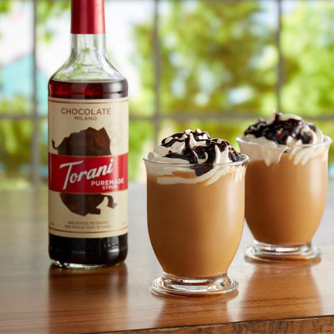 Coffee with cream on top and Puremade Syrup Chocolate Milano, in the background a bottle of Puremade Syrup Chocolate Milano, Torani