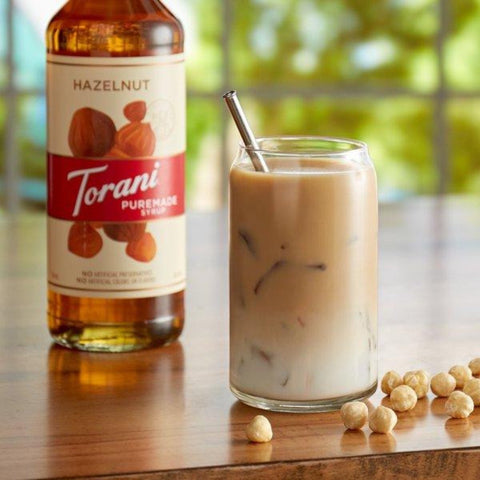 A glass of iced coffee with Puremade Syrup Hazelnut, in the background a bottle of Puremade Syrup Hazelnut, Torani
