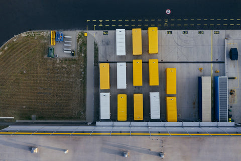 An aerial shot of yellow and white trucks, lined up outside a distribution center