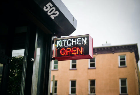 """Outside a city center restaurant, a neon sign reads: """"Kitchen open"""""""