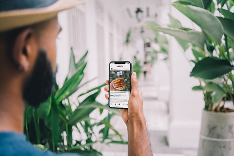 A man holds up a mobile phone with an Instagram post of a burger on it
