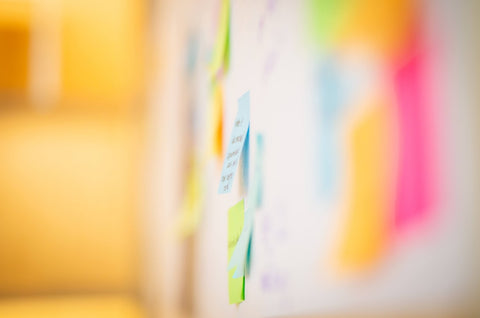 Out of focus shot of multi-colored Post-Its on a wall