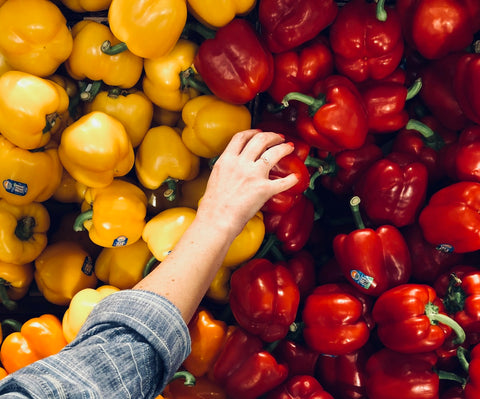 A woman's hand reaches for a red capsicum from a pile of red and yellow vegetables
