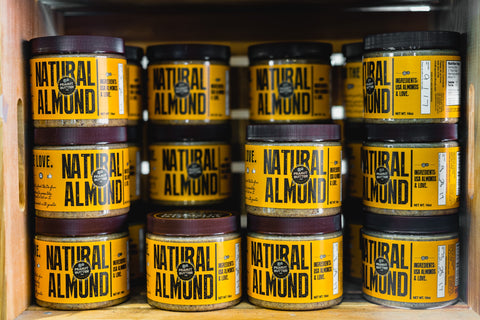 A stack of jars with yellow labels reading 'Natural almond'