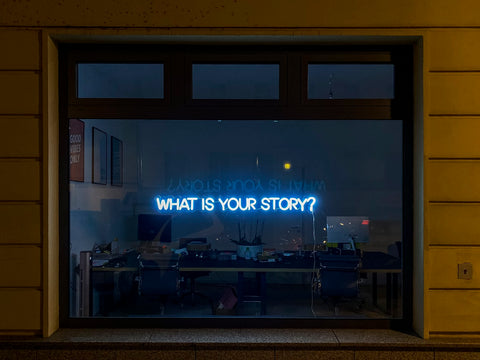 A dark lit office window with a blue neon light sign that reads 'What's your story?'