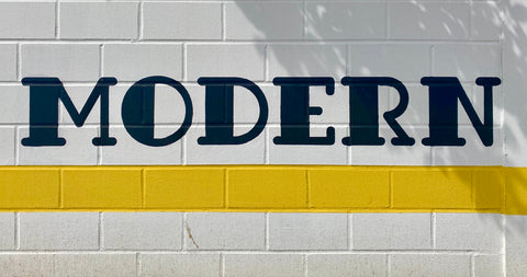 Hand-written wall sign in yellow, black and white that reads 'modern' in a serif typeface