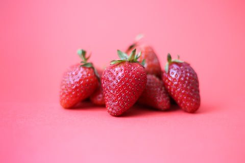 A small pile of strawberries set against a bubblegum pink background