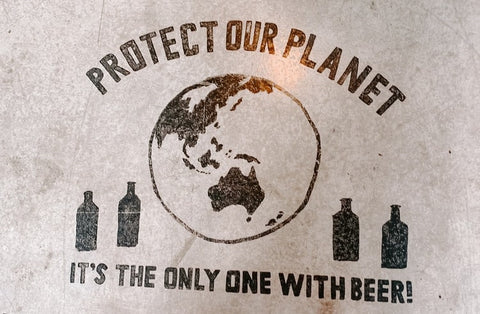 A floor sign that reads 'Protect our plant it's the only one with beer'