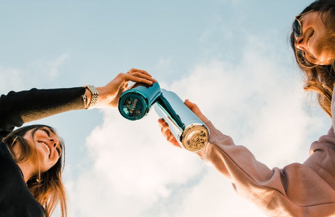 Two women cheers their KeepCups against a bright blue sky