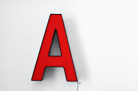 A red letter 'A' lamp against a white background