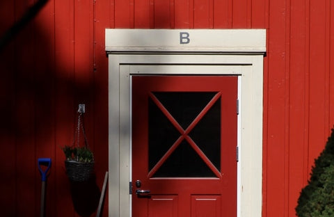 A red barn door with the letter 'B' above it