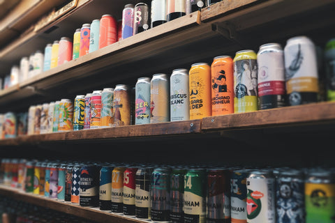 Colorful craft beer cans lined up on a wooden shelf
