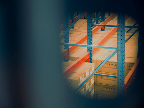 An image of a CPG distribution center with a stack of cardboard boxes in soft focus