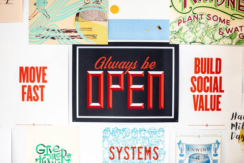 """A printed moodboard featuring inspiring sayings like """"Move fast"""", """"Build social value"""", and """"Always be open"""""""
