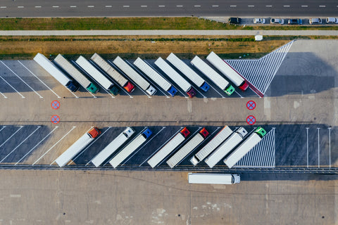 Seen from the sky, a car park of trucks lined up in a row