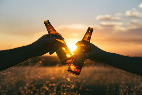 Two arms extended, clinking beer bottles in front of a sunset