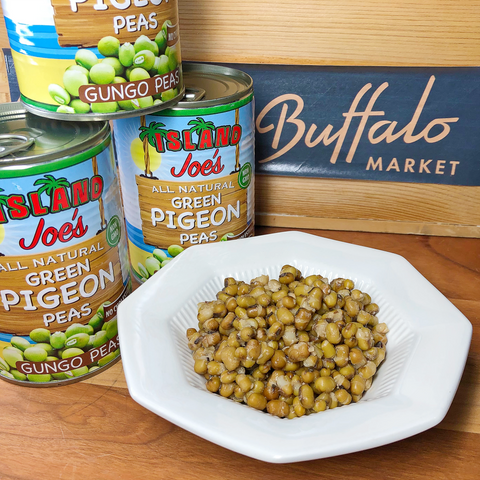 Non-GMO Green Pigeon Peas, Island Joe's on a plate, in the background cans of Green Pigeon Peas, Island Joe's