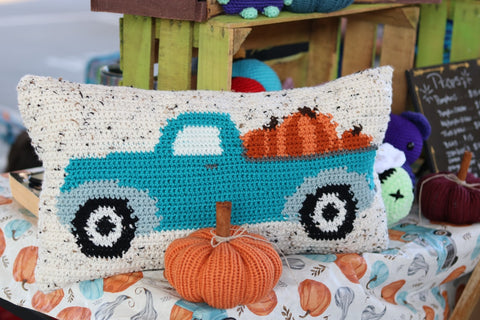 A farmer's truck with pumpkins in the back, cross-stitched onto a cushion