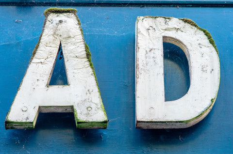 The letters 'AD' in big, white wooden letters on a blue wall