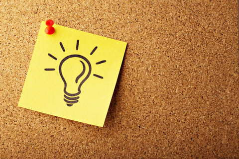 A yellow Post-It note with a lightbulb drawn on it, pinned to a brown corkboard