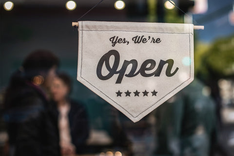 A store door sign that reads 'Yes, we're open'