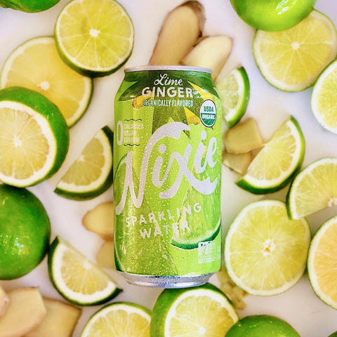 Can of Lime Ginger Sparkling Water on background of limes and ginger
