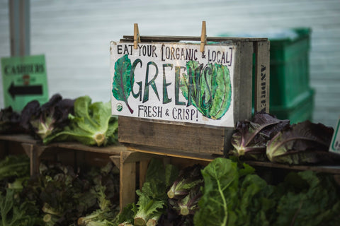 A farmers' market stall displaying lettuce and greens with a sign reading 'Eat your organic and local greens'
