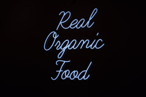 A light blue neon sign against a black background reading, in cursive, 'Real organic food'