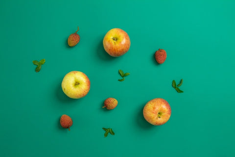A flat lay of apples, strawberries and leaves against a turquoise backdrop