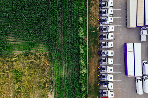 A aerial shot of distribution trucks parked in a lot next to a field