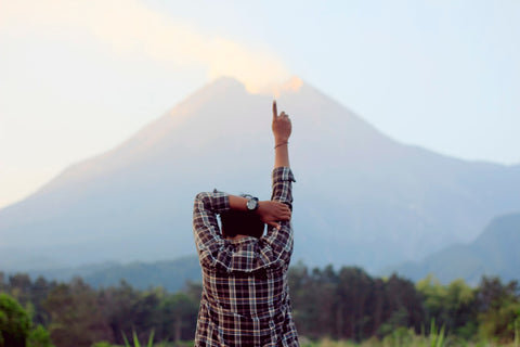 A man stands facing a rural landscape with one finger pointed up into the air