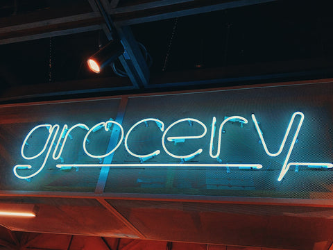 Blue neon sign that reads 'grocery'